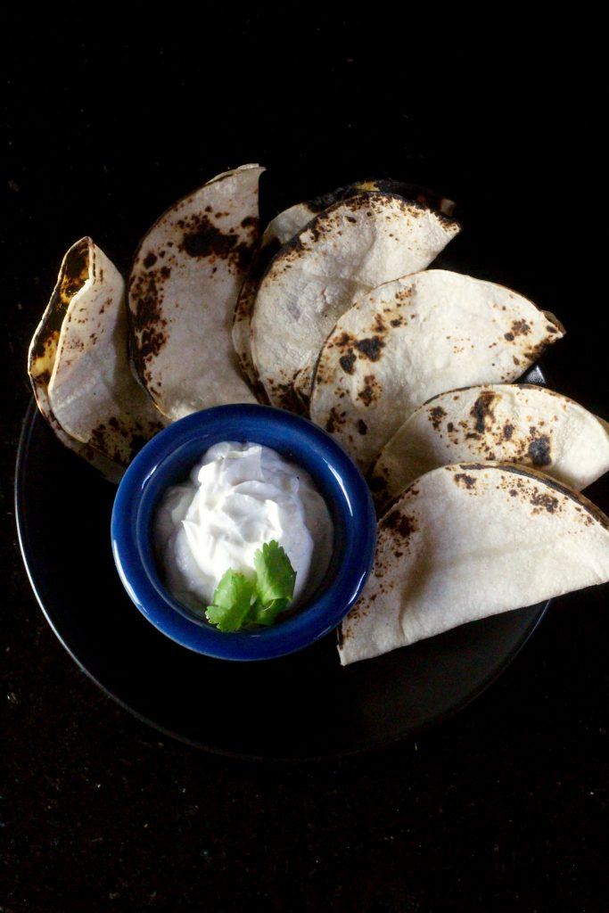 Smoky charred corn tortillas and sour cream